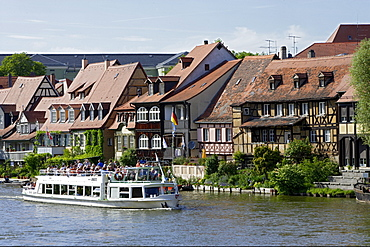 Tourist boat on river Regnitz in the houses of little Venice, Bamberg, Upper Franconia, Bavaria, Germany
