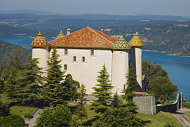 The castle of Aiguines with its coloured roof tiles in front of the lake Lac de Ste. Croix, Var, Provence, France