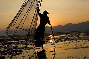 Intha fisherman on his fishing boat on Inle Lake at sunset, Shan State, Myanmar, Burma
