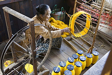 Old women of the Intha tribe working on a spinning wheel, Inle Lake, Shan State, Myanmar, Burma