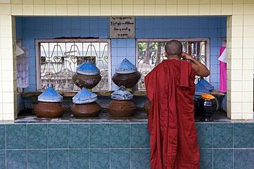 Buddhist monk drinking water at Mahagandhayon monastary in Amarapura near Mandalay, Myanmar, Burma