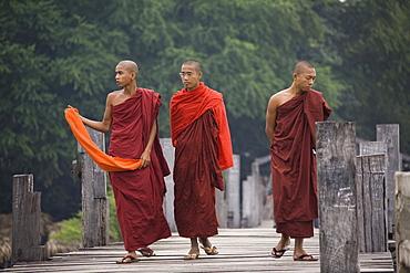 Three young buddhistic monks walking on the U Beins Bridgein Amarapura near Mandalay, Myanmar, Burma