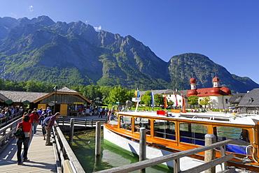 people on landing stage with boat, Watzmann range in background, St. Bartholomae, lake Koenigssee, Berchtesgaden range, National Park Berchtesgaden, Berchtesgaden, Upper Bavaria, Bavaria, Germany