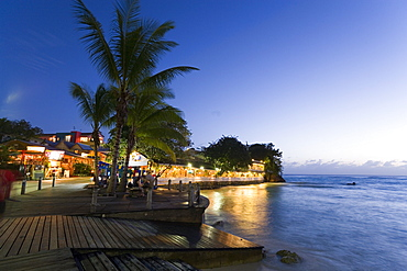 Tourists at promenade next to Pisces Restaurant at night, St. Lawrence Gap, Barbados, Caribbean