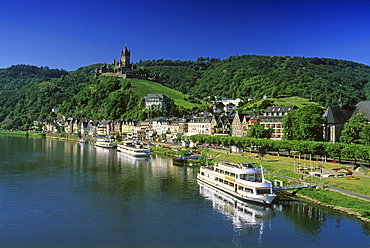 Reichsburg under blue sky and excursion boats at the riverbank, Mosel, Rhineland-Palatinate, Germany
