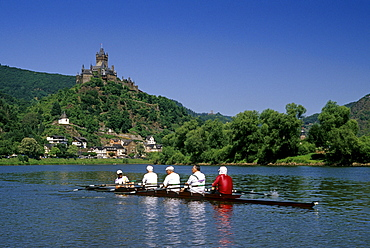 Reichsburg under blue sky and rowing boat on the river, Mosel, Rhineland-Palatinate, Germany