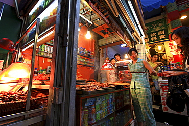 Typical little shop with sales woman in Chongqing, China, Asia