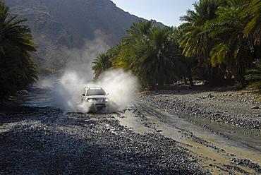 An all-terrain vehicle driving through a riverbed, Al Hajar mountains, Wadi Bani Auf, Oman, Asia