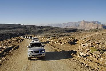 A row of all-terrain vehicles driving on a road through barren scenery, Al Hajar mountains, Oman, Asia
