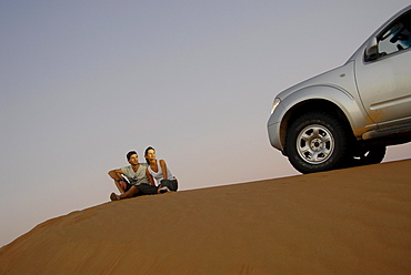 People and detail of an all-terrain vehicle on a dune, Wahiba Sands, Oman, Asia