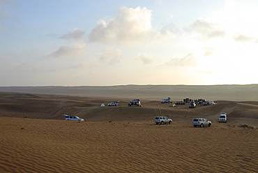 All-terrain vehicles standing in the sands of the desert at dawn, Wahiba Sands, Oman, Asia