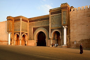 Locals in front of the town gate Bab el Mansour in the evening sun, Meknes, Morocco, Africa
