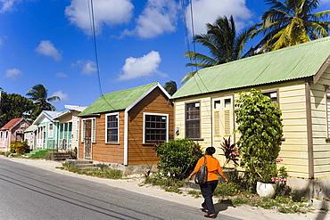 Woman walking along Chattel Houses, Six Men's Bay, Barbados, Caribbean