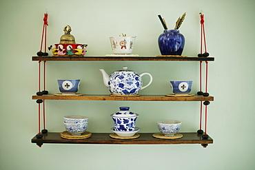 Decorated souvenir shelf with antique asian teapot, cups