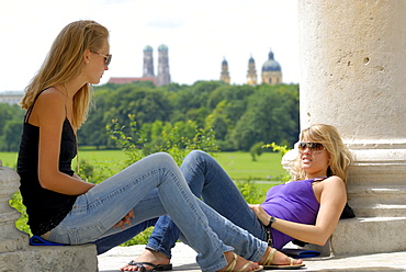Two young women sitting beneath Monopterus with view to churches Frauenkirche and Theatinerkirche out of focus in background, Englischer Garten, Munich, Upper Bavaria, Bavaria, Germany