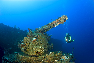 Diver at 5-inch Gun of USS Saratoga, Marshall Islands, Bikini Atoll, Micronesia, Pacific Ocean