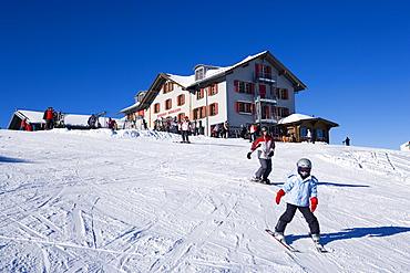 Skiers on slope, alpine lodge Maennlichen in background, Maennlichen, Grindelwald, Bernese Oberland, Canton of Bern, Switzerland