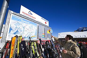Skier reading a map at mountain restaurant Schreckfeld, First, Grindelwald, Bernese Oberland, Canton of Bern, Switzerland
