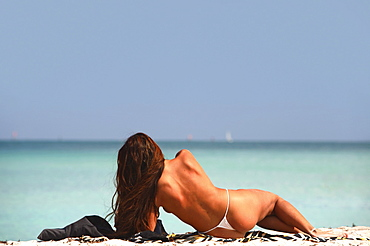 Woman sunbathing at the beach, South Beach, Miami Beach, Florida, USA