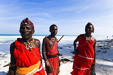 Three plastic Massai wearing traditional clothing at Diani Beach, Coast, Kenya