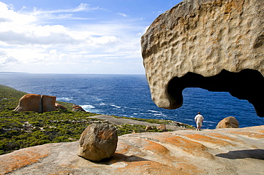 A man standing amidst the Remarkable Rocks at Flinders Chase National Park at the coast, Kangaroo Island, South Australia, Australia
