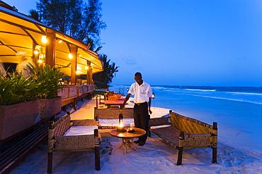 Waiter arranging lanterns, The Sands, at Nomad, Diani Beach, Kenya