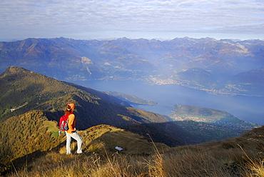 Woman enjoying view over lake Como, Monte Legnone, Bergamo Alps, Como, Lombardy, Italy
