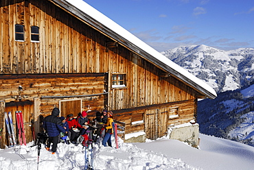 Backcounty skiiers resting at alpine hut, Wiedersberger Horn, Kitzbuehel Alps, Tyrol, Austria