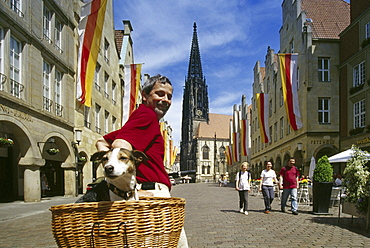 Cyclist with dog, Prinzipal market, Muenster, Muensterland, North Rhine-Westphalia, Germany