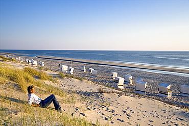 Woman sitting on beach, Rantum, Sylt Island, Schleswig-Holstein, Germany