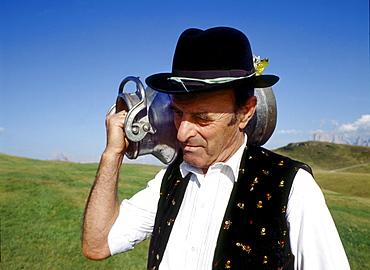 A man wearing traditional costume carrying a milk can on his shoulder, South Tyrol, Italy, Europe