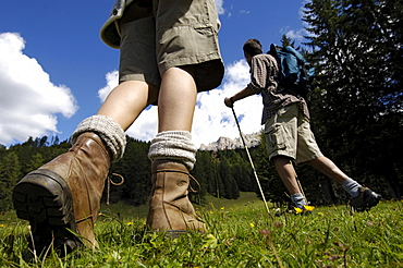 A woman and a man hiking in the mountains, South Tyrol, Italy, Europe