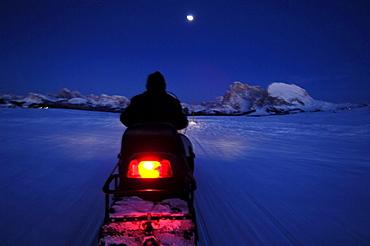 Man on a skidoo at night, Langkofel Mountain Range, South Tyrol, Italy