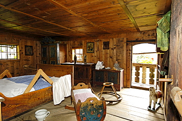 The farmhouse bedroom with bed, cradle and rocking horse, South Tyrolean local history museum at Dietenheim, Puster Valley, South Tyrol, Italy