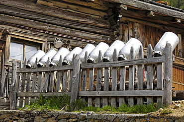 Milk churns on a wooden fence in front of alpine hut, Schnals valley, Val Venosta, South Tyrol, Italy, Europe
