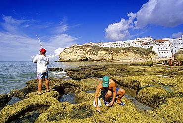Angler and shell seaker on the beach under blue sky, Carvoeiro, Algarve, Portugal, Europe