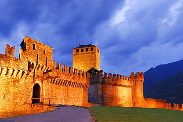 Illuminated castle Castello di Montebello with draw bridge in UNESCO World Heritage Site Bellinzona, Bellinzona, Ticino, Switzerland