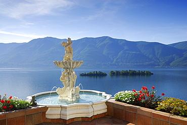 Lake Maggiore with isle of Brissago, Isole di Brissago, and Monte Gambarogno with fountain and flowers in the foreground, Ronco sopra Ascona, lake Maggiore, Lago Maggiore, Ticino, Switzerland