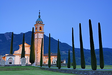 Illuminated church San Abbondino near Gentilino with cypress alley, Gentilino, Lugano, Ticino, Switzerland