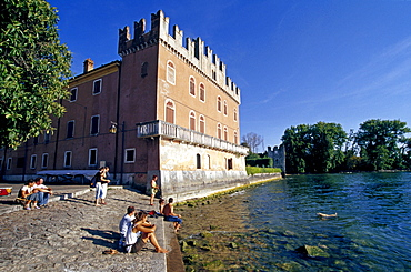 People sitting at the lakeside at the Scaliger castle, Lazise, Lake Garda, Veneto, Italy, Europe