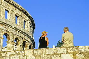 Couple on the city wall in front of the Roman amphitheater under blue sky, Pula, Croatian Adriatic Sea, Istria, Croatia, Europe