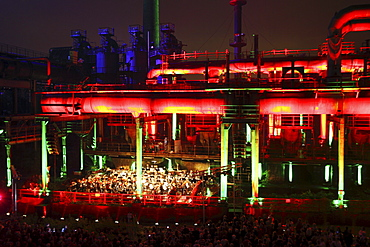 The Duisburg Philharmonic Orchestra playing in front of the illuminated backdrop of the Huette Meiderich, Duisburg, Ruhr Area, North Rhine-Westphalia, Germany, Europe
