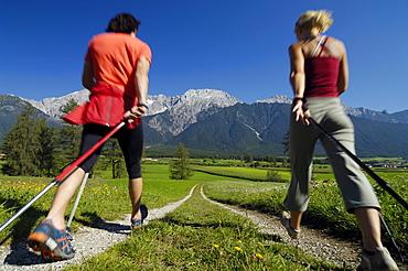 Young couple nordic walking in an idyllic landscape, Tyrol, Austria, Europe