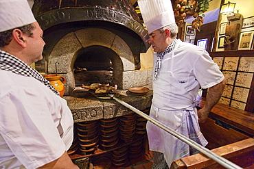 Cooks preparing roast lamb in a wood-fired oven, La posada de la Villa, Cava Baja, Madrid, Spain