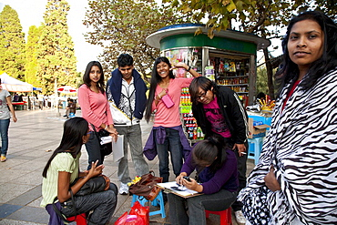 Portrait drawer and foreign students at Green Lake Park, Kunming, Yunnan, People's Republic of China, Asia