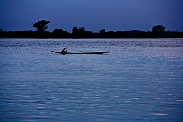 Man paddling in dug out canoe on the river Niger in the evening, Sagou, Mali, Africa
