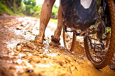 Woman pushing a mountainbike through mud, Masoala National Park, Madagascar