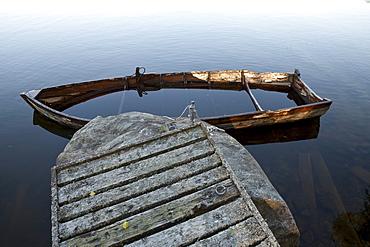 Half sunken wooden rowing boat at a jetty, island of Norrbyskaer, Vaesterbotten, Sweden, Europe