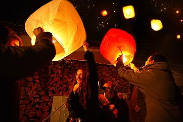 People lighting skylaterns on new year, Munsing, Bavaria, Germany