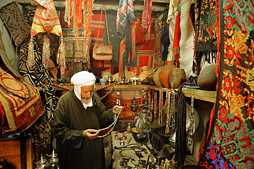 Vendor in the souq in his shop selling typical goods from the Sahara region, Marrakech, Morocco, Africa